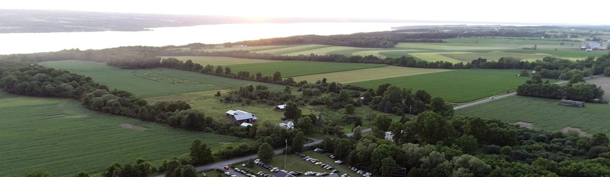 Aerial view of Treleaven Winery in King Ferry, NY, with sunset over Cayuga Lake in the background